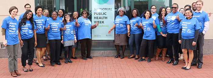 APHA staff members standing in front of NPHW sign