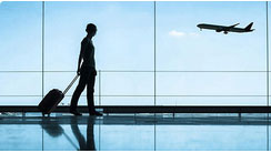 silhouette of woman walking in airport with suitcase