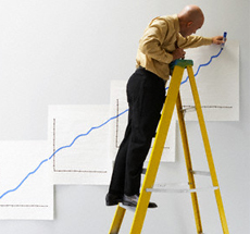 Man on ladder drawing graphs