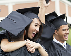 smiling teens in caps and gowns