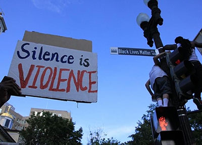 Silence is Violence protest sign near Black Lives Matter street sign