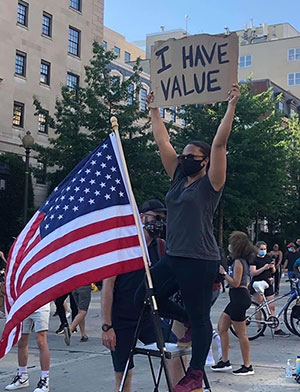 masked black woman at protest holding up I Have Value sign next to American flag