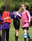A group of young girls in soccer uniforms shaking hands